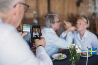 Senior man photographing couple having drinks in restaurant - MASF01071