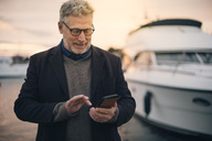 Senior man using smart phone while standing at harbor - MASF01074