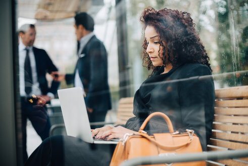 Side view of mid adult businesswoman using laptop sitting at bus shelter seen from glass - MASF01098