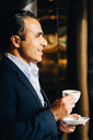 Side view of smiling mature businessman holding coffee cup while looking away at cafe - MASF01104