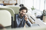 Smiling male professional talking through mobile phone while sitting on chair at creative office - MASF01128