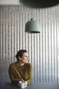 Smiling businesswoman sitting with coffee cup at desk against corrugated iron wall - MASF01131
