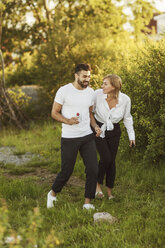 Smiling young couple talking while walking on grassy field - MASF01167