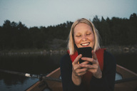 Smiling woman using mobile phone while sitting in boat on lake - MASF01179