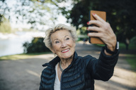 Smiling senior woman taking selfie with smart phone in park - MASF01194