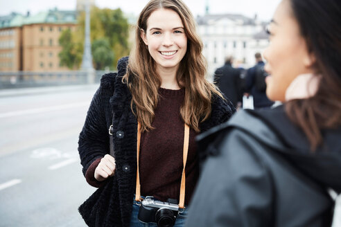 Smiling woman standing with friend by street in city - MASF01233