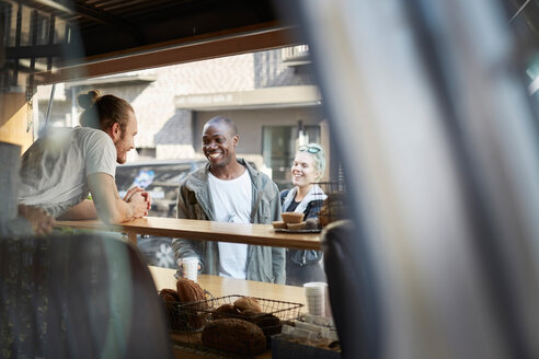 Smiling mid adult man talking with salesman at food truck - MASF01248