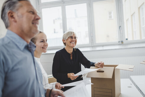 Smiling mature businessman with colleague unpacking cardboard box in new office - MASF01257