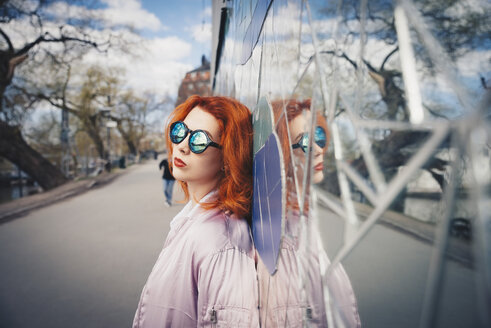 Redhead young woman wearing sunglasses while leaning on mosaic wall by street - MASF01271