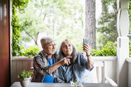 Senior couple taking selfie in porch - MASF01295