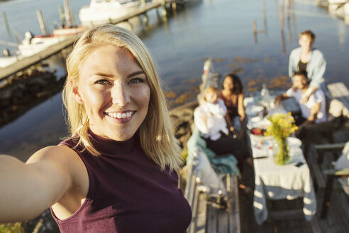 Portrait of smiling young woman with friends in background at jetty - MASF01298