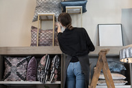 Rear view of young female entrepreneur standing on ladder while arranging cushion in rack at store - MASF01304