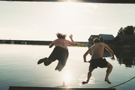 Rear view of shirtless friends diving in lake against sky on sunny day - MASF01307