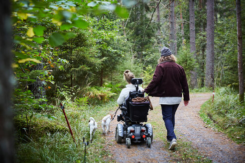 Rear view of male caretaker with disabled woman and dog in forest - MASF01313