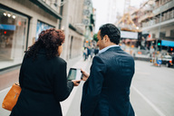 Rear view of businesswoman showing digital tablet to businessman while walking on sidewalk in city - MASF01340