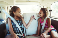 Girl showing smart phone to sister while traveling in car - CAVF35246