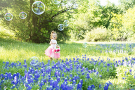 Smiling girl looking at bubbles while standing by flowers blooming on field - CAVF35261