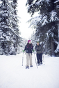 Couple snowshoeing in forest - CAVF35282