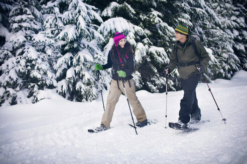 Couple snowshoeing in forest - CAVF35291