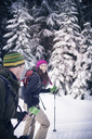 Couple snowshoeing in forest - CAVF35294