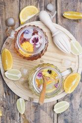 Refreshing mineral water with edible flowers, Viola wittrockiana, Dianthus caryophyllus, Calendula officinalis, lemon and orange - SKCF00412