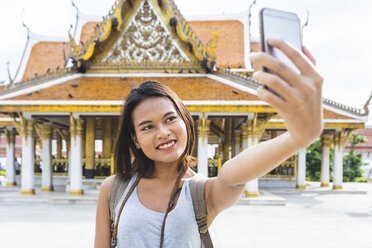 Thailand, Bangkok, portrait of smiling tourist taking selfie with smartphone - WPEF00182