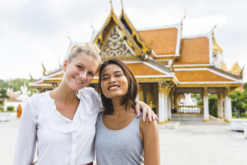Thailand, Bangkok, portrait of two smiling friends in front of temple - WPEF00191