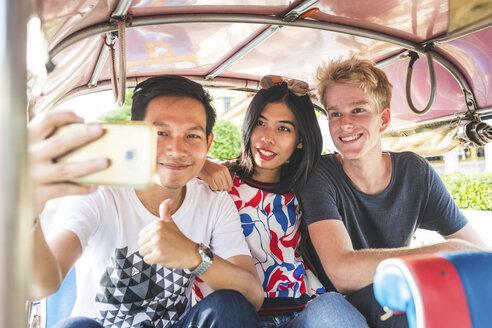 Thailand, Bangkok, three friends riding tuk tuk taking selfie with smartphone - WPEF00194
