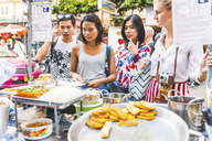 Thailand, Bangkok, Khao San Road, group of friends choosing local food on street market - WPEF00200