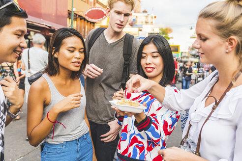 Thailand, Bangkok, Khao San Road, group of friends tasting local food on street market - WPEF00203