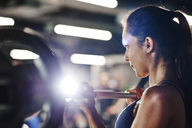 Woman lifting barbell in gym - ABIF00238