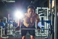 Man lifting barbell in gym - ABIF00241
