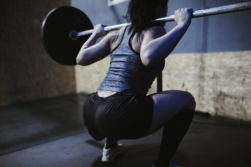 Woman lifting barbell in gym - ZEDF01260