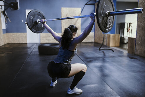 Woman lifting barbell in gym - ZEDF01266
