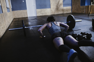 Woman doing push ups at barbell in gym - ZEDF01272