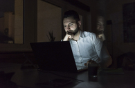 Businessman working on laptop in office at night - UUF13196