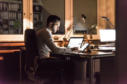 Businessman working at desk in office at night - UUF13199