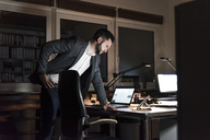 Businessman standing in office at night looking at tablet - UUF13202
