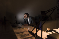 Pensive young businessman sitting at desk in office at night - UUF13208