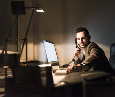 Businessman on the phone in office at night - UUF13211
