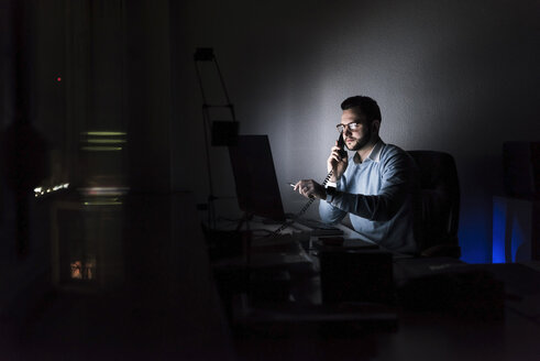 Businessman on the phone in office at night - UUF13217