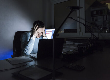 Tired businessman sitting at desk in office at night - UUF13220