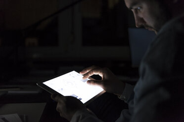 Businessman working on tablet in the dark, close-up - UUF13226