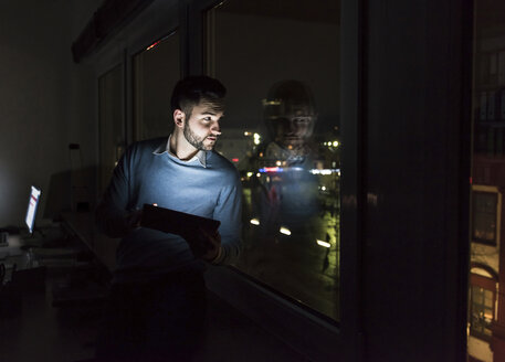 Businessman sitting with tablet on window sill in office at night looking out of the window - UUF13229