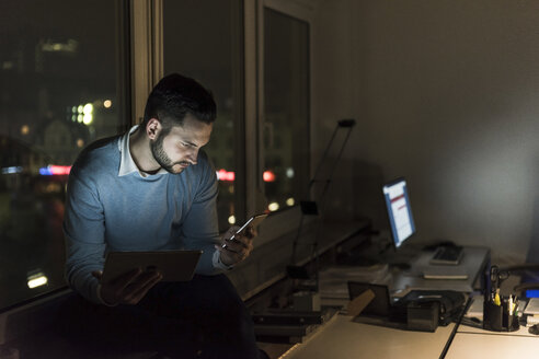 Businessman sitting on windowsill in office at night looking at smartphone - UUF13232