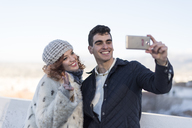 Portrait of happy young couple taking selfie with smartphone - JASF01867
