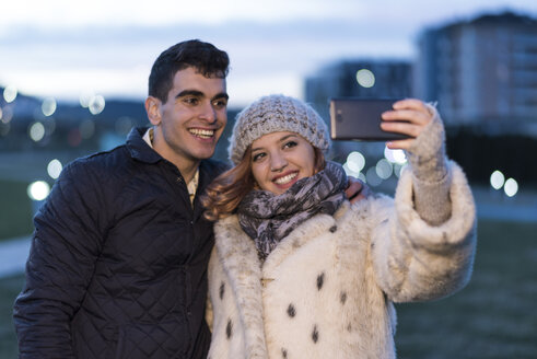 Portrait of happy young couple taking selfie with smartphone in the evening - JASF01885