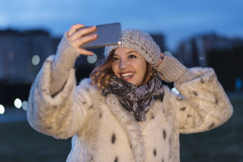 Laughing young woman taking selfie with smartphone at evening twilight - JASF01888