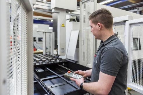 Man operating machine in factory - DIGF03683