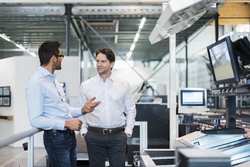 Two businessmen talking in modern factory - DIGF03698